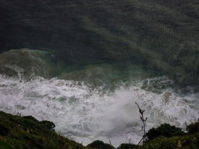 Wellen brechen sich an den Felsen am Cape Reinga