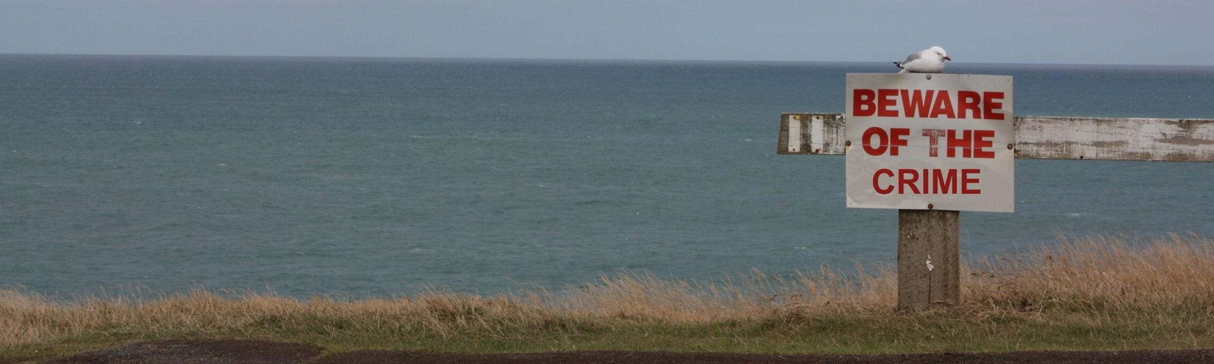 Warnschild vor einem Steilhang mit Möwe auf Neuseeland