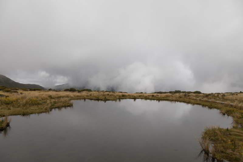 Ein See im Vordergrund und im Hintergrund Wolken.