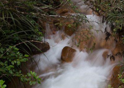 Das Wasser rauscht den schmalen Bach hinab, über einem farbenfrohen orangen Flussbett.